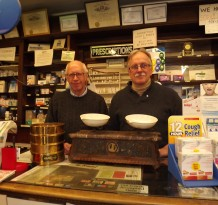 Cousins James Potrepka, left, and Chester Potrepka Jr., co-owners of Plantsville Pharmacy, show an antique balance weighing device that their fathers used when the pharmacy was established in April 1946. Now one of the oldest commercial businesses in downtown Plantsville, it will celebrate its 70th anniversary in 2016.